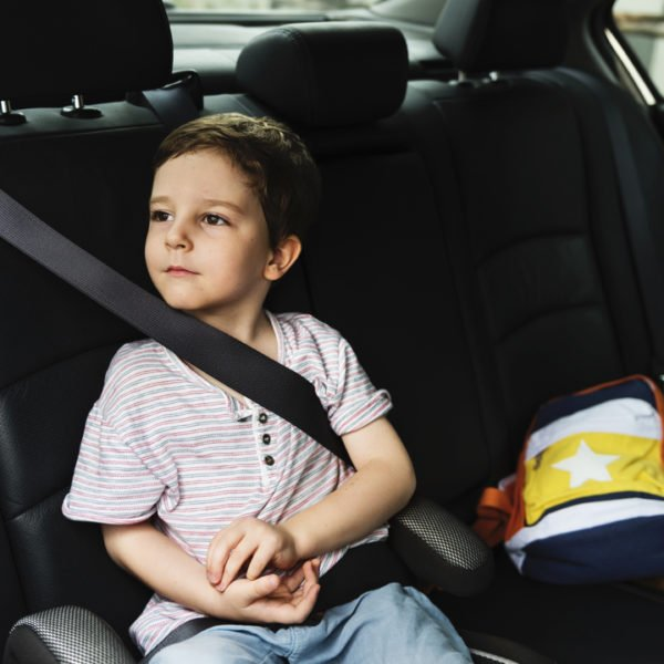 Young boy with light skin and dark hair sitting in a car using a booster seat