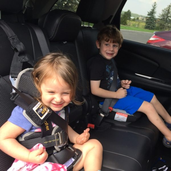 folding car seat for travel: young girl in foreground in Ride Safer travel vest, young boy in background sitting on Bubblebum inflatable booster seat