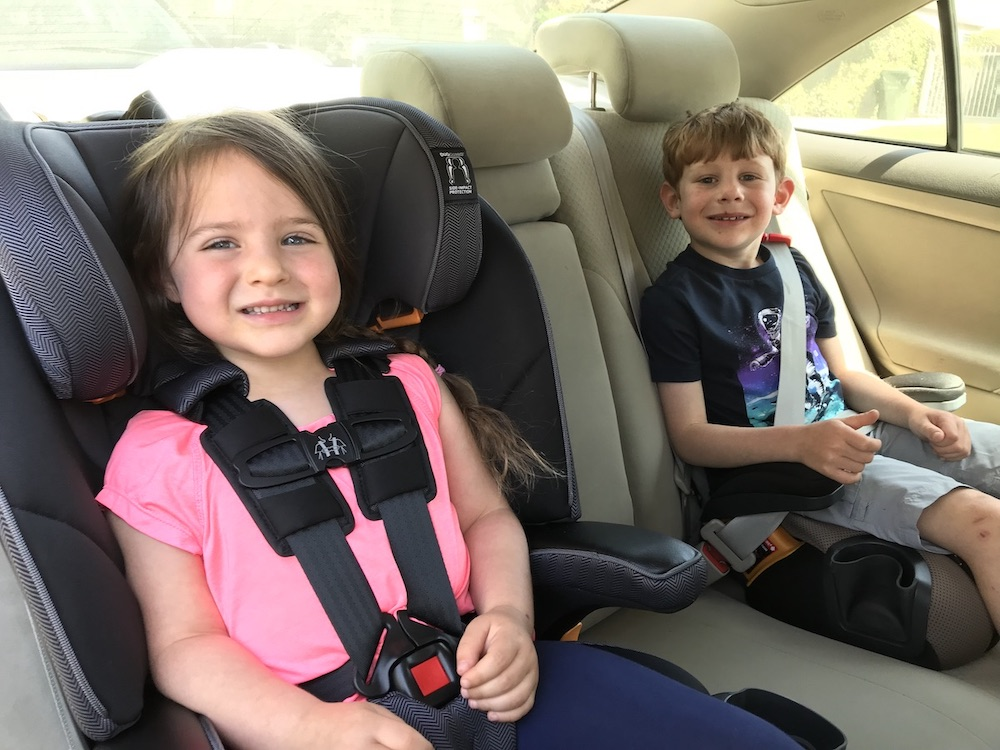 left: young girl in pink shirt riding in a black Chicco MyFit car seat; right: young boy in navy shirt riding in Chicco GoFit+ booster seat