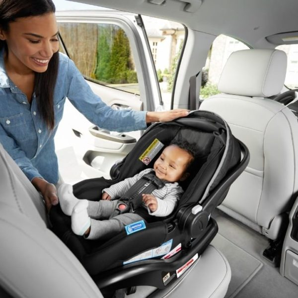 Mother adjusting infant riding in Graco SnugRide SnugLock infant car seat
