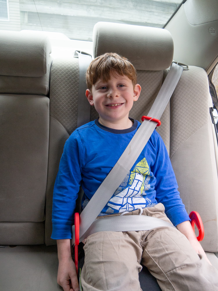 Young boy in blue shirt and tan pants buckled in a tan car, sitting on a Graco Turbo Go backless booster seat with red seatbelt guides visible