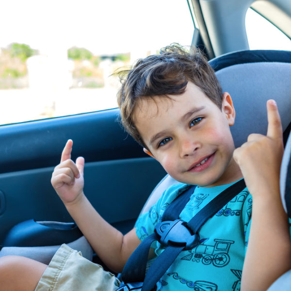 Young boy in blue shirt sitting in forward facing car seat