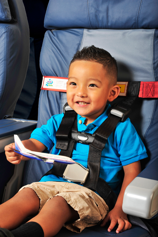 Young boy in blue shirt holding toy airplane while secured in the AmSafe CARES child restraint