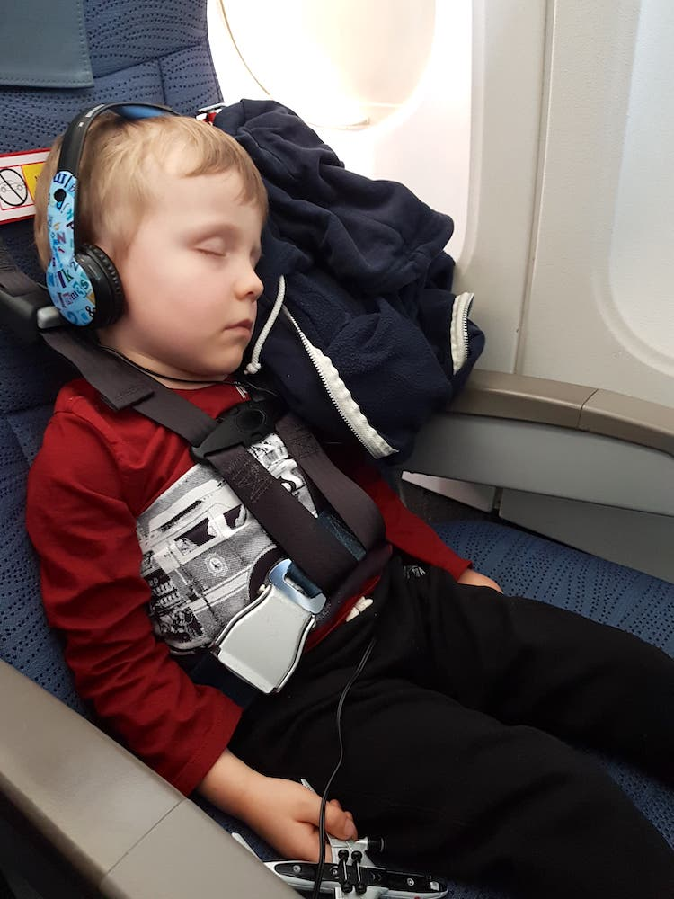 Boy in red sweater asleep while restrained with the CARES toddler airplane seatbelt