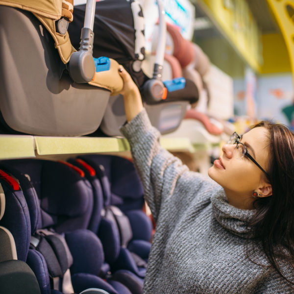 woman reaching to look at best cheap car seats under $100