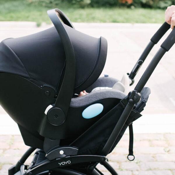 Clek liing car seat on a Babyzen Yoyo stroller, two hands pushing stroller